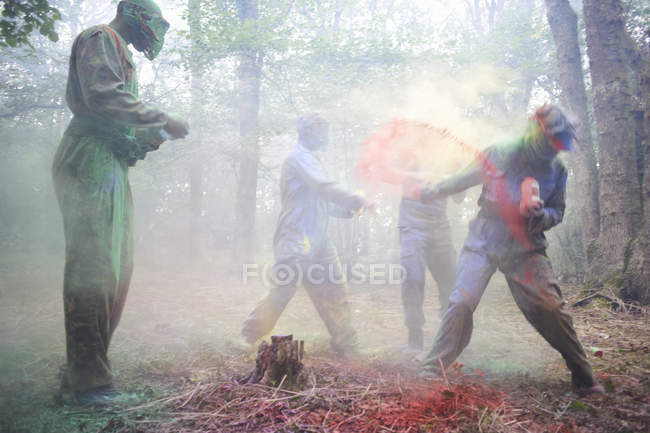 Paintball players in action with colorful paints in woods — Stock Photo