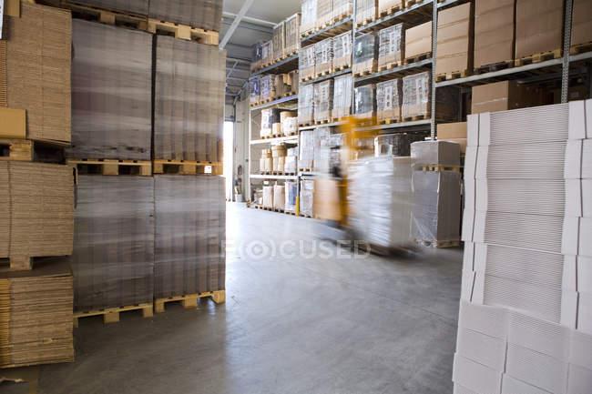 Розмиті навантажувача вантажівку в склад для зберігання — стокове фото