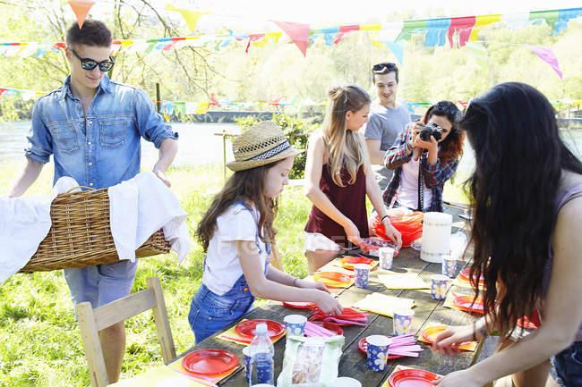 Piccolo gruppo di giovani amici adulti che allestiscono un tavolo da picnic in giardino — Foto stock