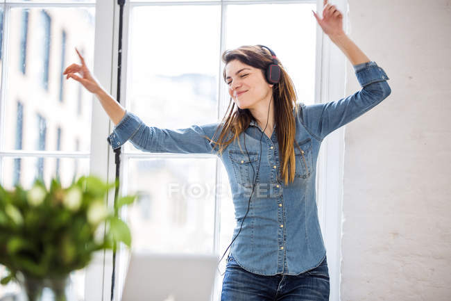 Young woman with eyes closed dancing in front of city apartment window — Stock Photo