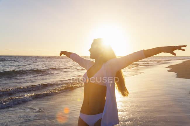 Giovane donna che balla a braccia aperte sulla spiaggia al tramonto, Repubblica Dominicana, Caraibi — Foto stock