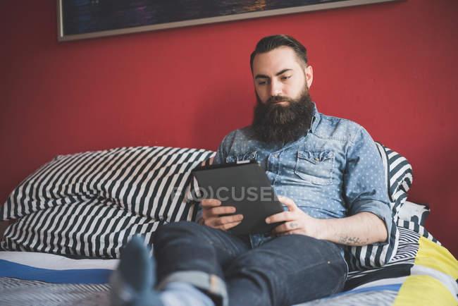 Молодой бородатый человек с помощью цифровой таблетки на кровати — стоковое фото
