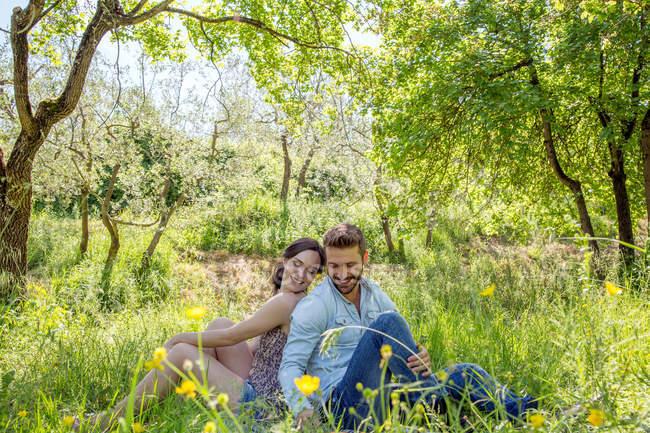 Sessão jovem casal de costas na grama, olhando para baixo sorrindo — Fotografia de Stock
