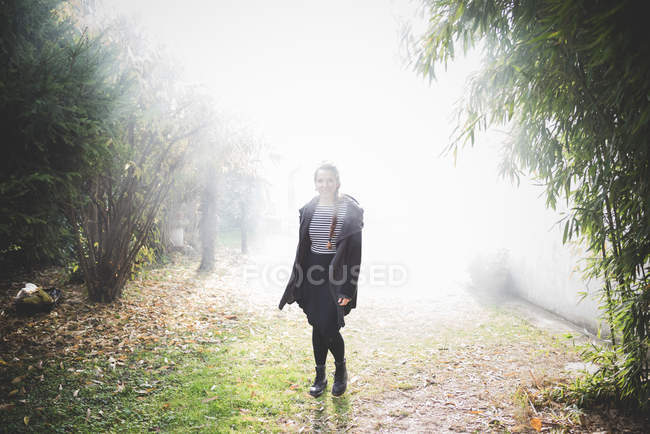 Повна довжина фронтальний вид молода жінка, стоячи в туманний саду переглядає камери посміхається — стокове фото
