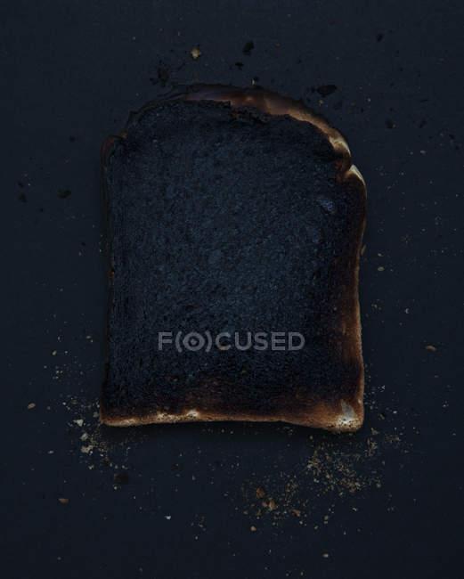 Вид зверху скибочку спалені тосту на темні настільні — стокове фото