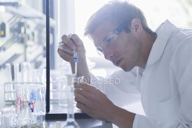 Молодий чоловічий вчений піласінг в склянку в лабораторії — стокове фото