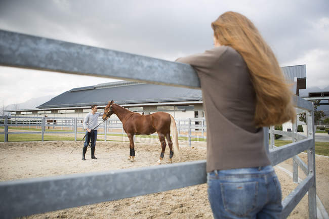 Jeune femme regardant stablehand train cheval dans paddock ring — Photo de stock