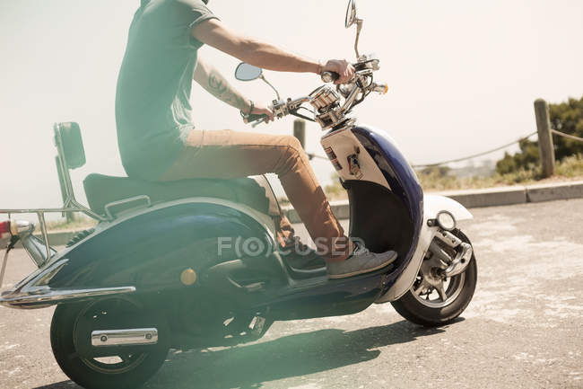 Mid adult man riding moped, low section — Stock Photo