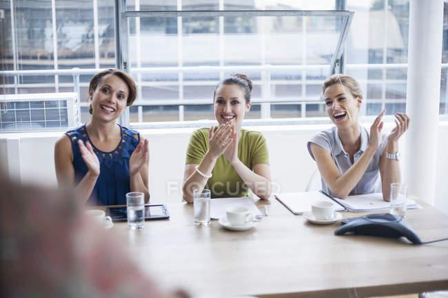 Trois femmes d'affaires applaudissant à la présentation au bureau — Photo de stock