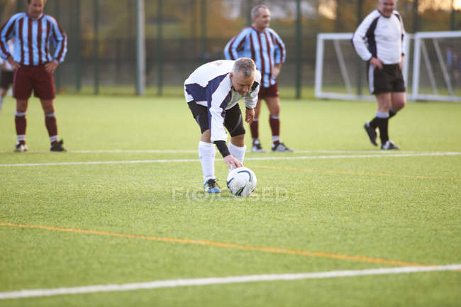Football player positioning ball on field — Stock Photo