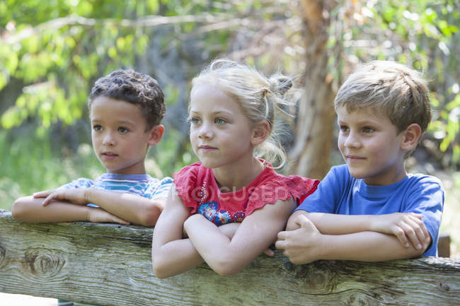 Three children leaning on fence and looking away — Stock Photo