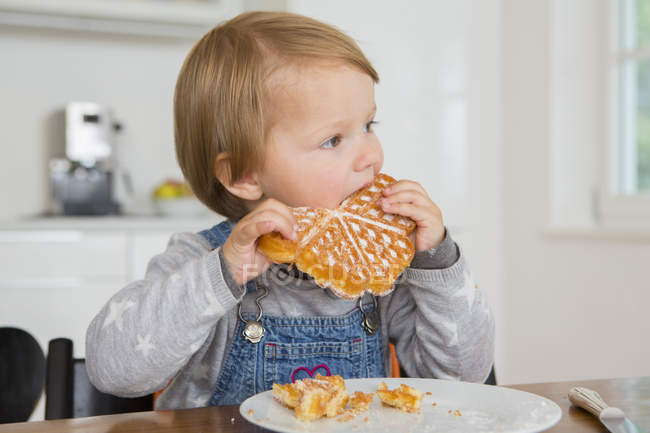Cute female toddler eating cake at kitchen table — Stock Photo