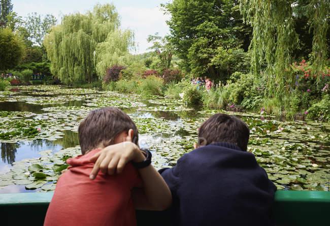 Vista posteriore di due giovani fratelli che guardano giù dal ponte pedonale al laghetto dei gigli — Foto stock