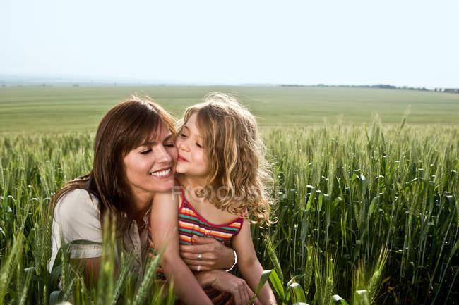Мати цілує дитину на пшеничному полі. — стокове фото