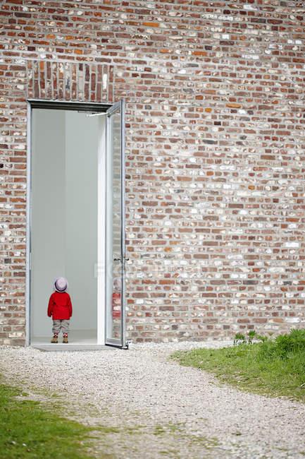 Jeune fille debout dans la porte dans le mur de briques — Photo de stock