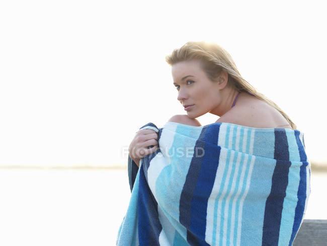 Jeune femme enveloppée dans une serviette de plage et embrassant les genoux, Altona, Melbourne, Victoria, Australie — Photo de stock