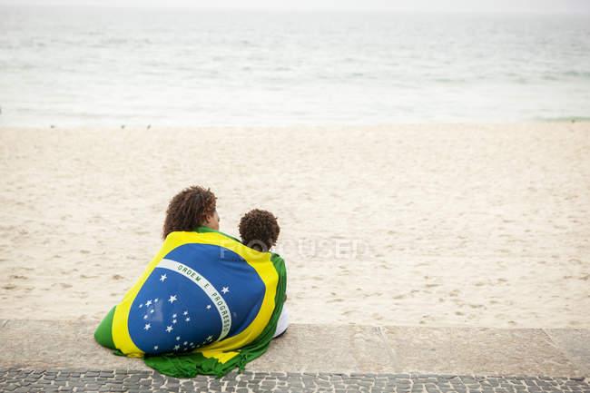 Veduta posteriore di giovane madre e figlio avvolto nella bandiera brasiliana sulla spiaggia di Ipanema, Rio De Janeiro, Brasile — Foto stock