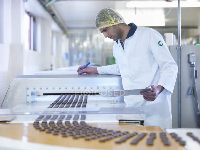 Працівник інспектування шоколаду на виробничій лінії в шоколадній фабриці — стокове фото