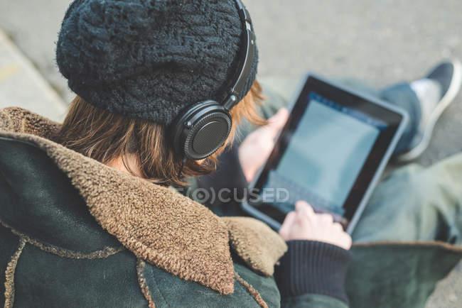 Человек с цифровым планшетом на бордюре, Милан, Италия — стоковое фото