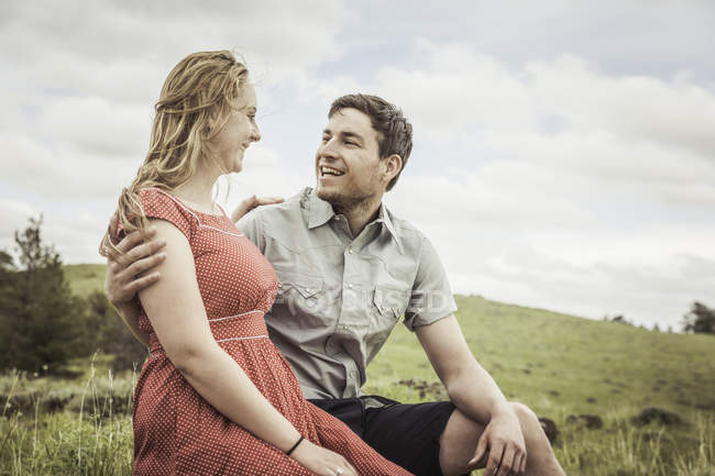 Happy young couple sitting on hillside, Cody, Wyoming, USA — Stock Photo