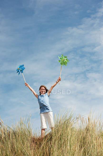 Menina segurando moinhos de vento no céu — Fotografia de Stock