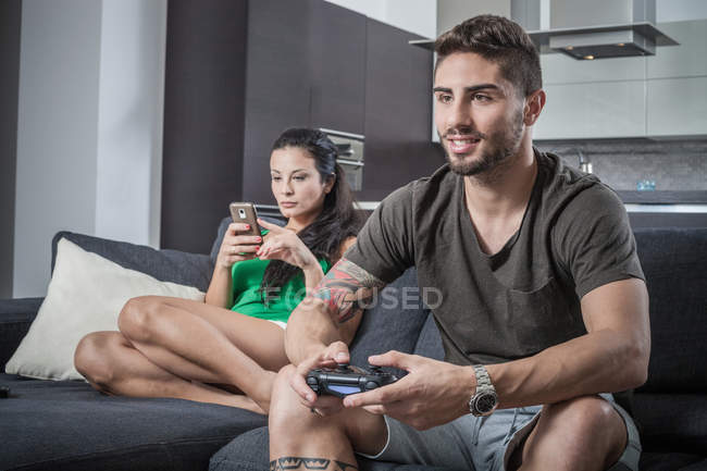 Young couple on sofa using smartphone and gaming control — Stock Photo