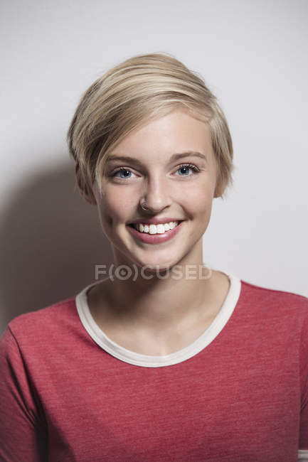 Studio portrait of happy young woman with short blond hair — Stock Photo