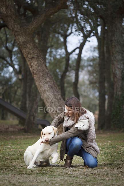 Giovane donna e cane nella foresta — Foto stock