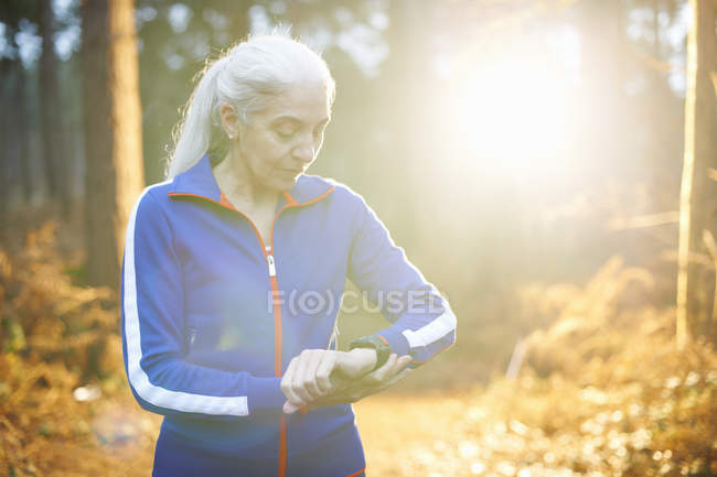 Mature woman wearing tracksuit top checking the time — Stock Photo