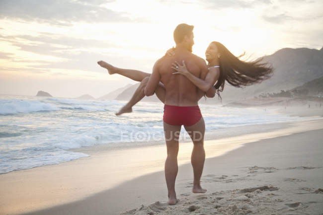 Mid adult couple on beach,man carrying woman in arms, rear view — Stock Photo