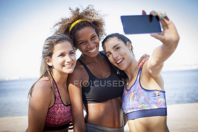 Three young women photographing themselves with phone — Stock Photo