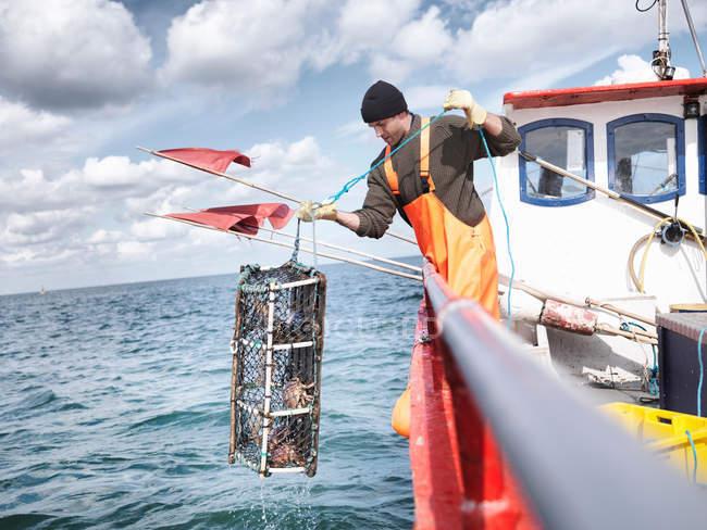 Pêcheur tirant le pot de homard avec des crabes — Photo de stock