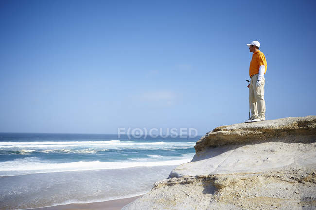 Low angle view of golfer standing on cliff overlooking ocean looking away — Stock Photo