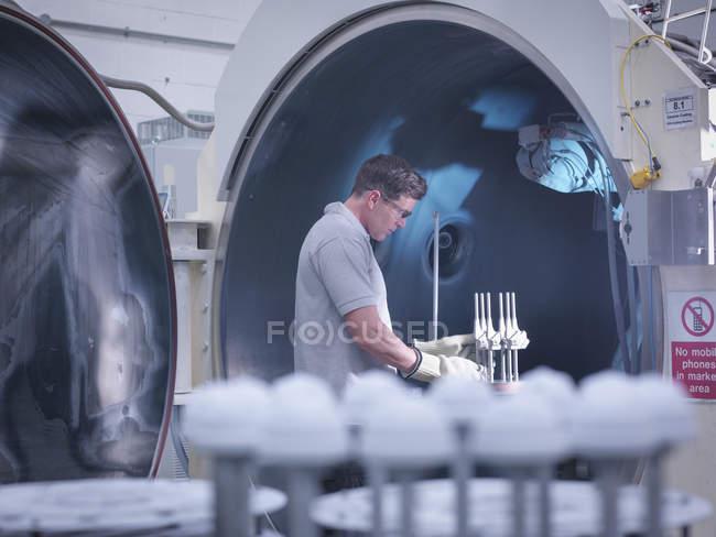 Ingénieur avec machine de revêtement en céramique, revêtement des articulations de hanche artificielles dans l'usine orthopédique — Photo de stock