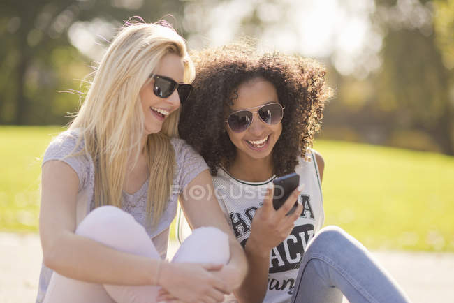 Two young female looking down at text message on smartphone in park — Stock Photo