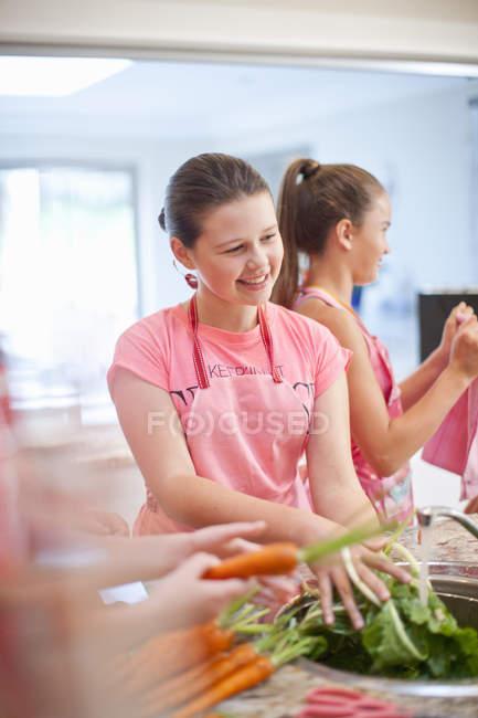 Девочки-подростки готовят морковь на кухне — стоковое фото