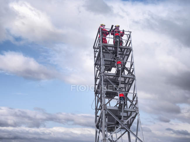 Two tower workers on offshore radio tower on windfarm, low angle view — Stock Photo