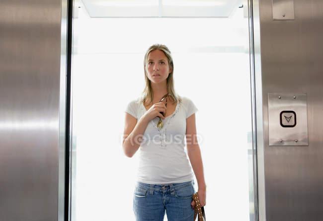 Jovem mulher caucasiana de pé no elevador — Fotografia de Stock