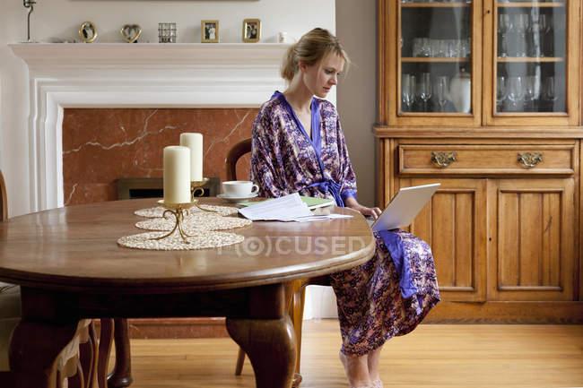 Молода жінка вдома в халат, працюючи на ноутбук — стокове фото