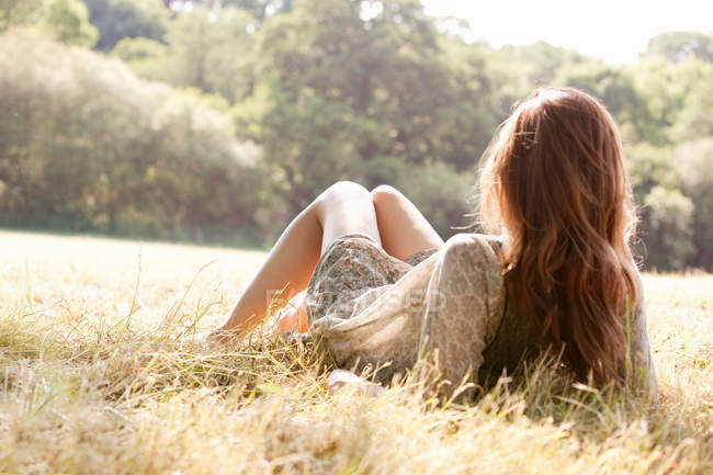 Woman lying in countryside field — Stock Photo