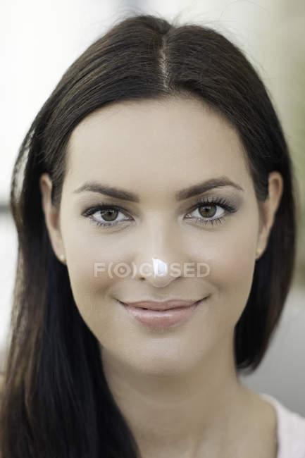 Ritratto di giovane donna con una piccola quantità di crema sul suo radiatore anteriore — Foto stock