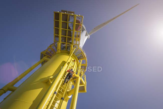 Ingegnere arrampicata turbina eolica dalla barca al parco eolico offshore, vista a basso angolo — Foto stock