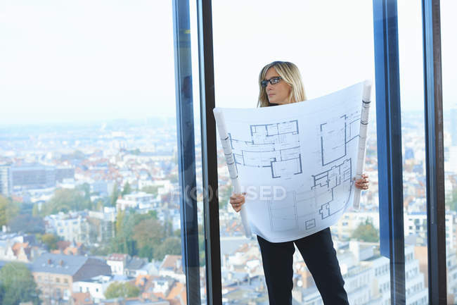 Mature architect in front of office window with Brussels cityscape, Belgium — Stock Photo