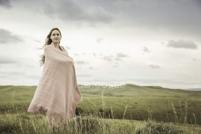 Young woman wrapped in pink blanket on hilltop, Cody, Wyoming, USA — Stock Photo