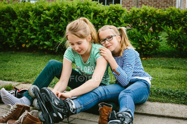 Two sisters sitting on sidewalk putting on rollerblades — Stock Photo