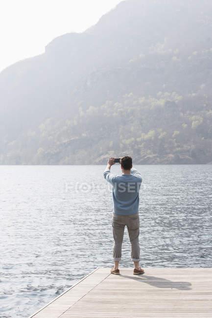 Вид сзади на молодого человека, фотографирующего с пирса, озеро Мергоццо, Вербания, Пьемонте, Италия — стоковое фото