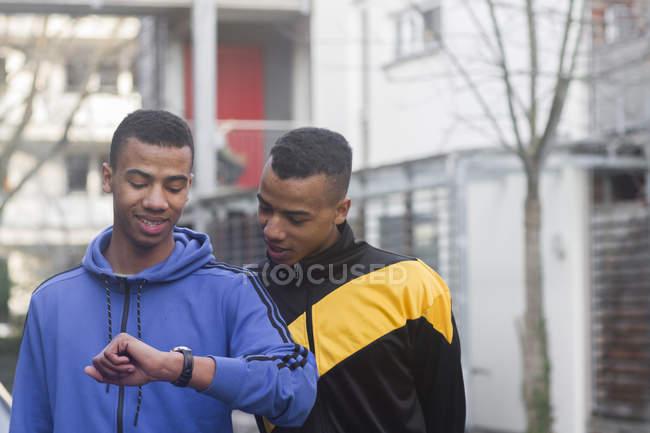Братья-близнецы идут по улице, глядя на часы — стоковое фото