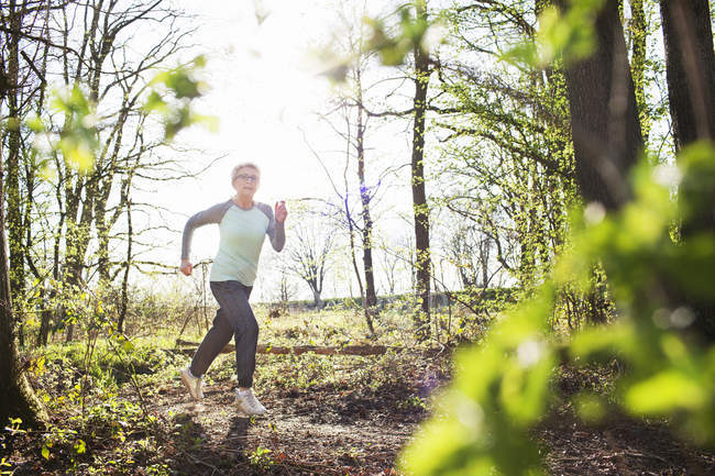 Sporty senior woman running in forest — Stock Photo