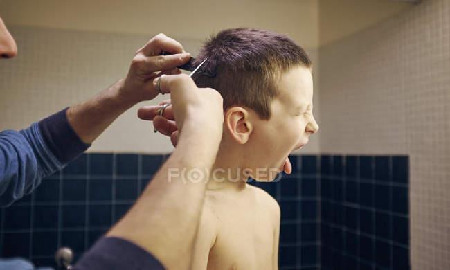 Отец стрижет неохотно сыновей волосы в ванной комнате — стоковое фото