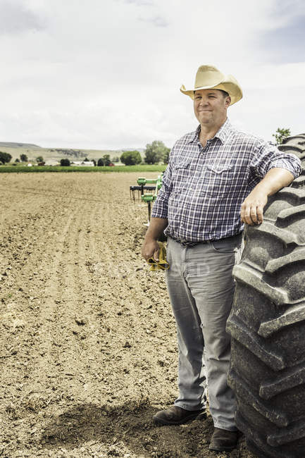 Portrait of male farmer leaning against tractor tyre in ploughed field — Stock Photo